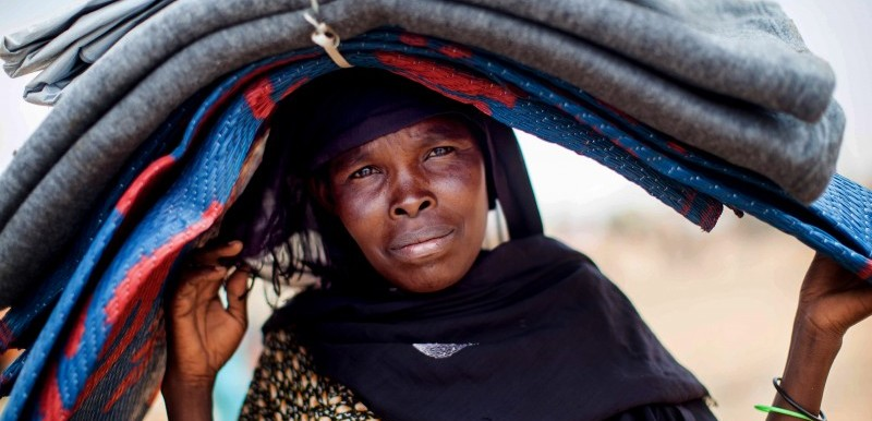 A woman carries blankets and carpets on her head at the Zamzam camp for displaced people in North Darfur, 2014 (Albert González Farran/Unamid)
