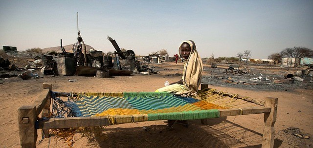 A displaced girl sits on a bed next to the remnants of her burnt house in Khor Abeche, South Darfur, April 2014 (Albert González Farran / UNAMID)