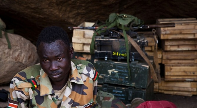Rebel soldier sits amongst ammunition that was taken from the Sudan Armed Forces (SAF) during fighting in the Nuba Mountians (SPLM-N)