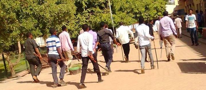 Students carry sticks to attack a group of students in Khartoum (RD)