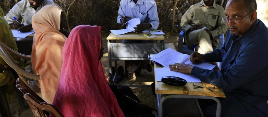 Special Prosecutor for Crimes in Darfur, Yasir Ahmed Mohamed (R), and his team talk to women during an government investigation into allegations of mass rape in the village of Tabit, North Darfur, November 20, 2014 (Reuters/Mohamed Nureldin Abdallah)
