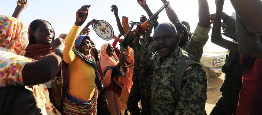 Women welcome a military convoy of government forces accompanying Special Prosecutor for Crimes in Darfur Yasir Ahmed Mohamed and his team after they arrived in Tabit village in North Darfur, November 20, 2014 (Mohamed Nureldin Abdallah/Reuters)