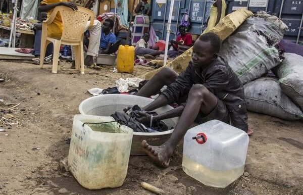 Photo: A teenager displaced by recent violence washes clothes in a basin at a UN compound in South Sudan (K. McKinsey / UNHCR)