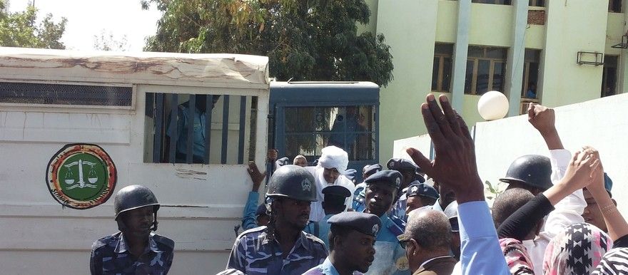 Supporters welcome Faroug Abu Eisa (wearing a white turban) as he disembarks from the police lorry.
