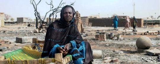 A displaced woman sits on a bed next to the remnants of her burnt house in Khor Abeche, March 2014 (Unamid)