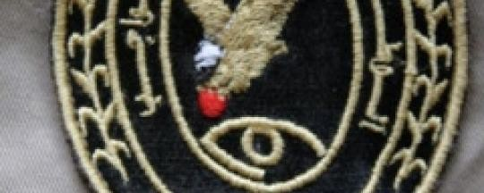 The patch used by the Central Reserve Police (Abu Tira) shows an eagle clutching a red sun, over an Eye of Horus. The Arabic text below reads, 'Central Reserve Police in Service of the People' (Enough Project)