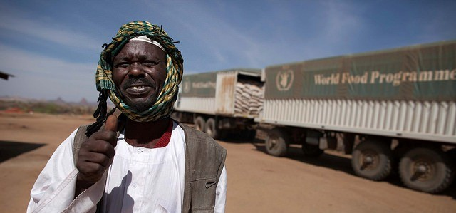 A community leader of Naivasha camp in North Darfur welcomes the arrival of WFP lorries to the camp (Albert González Farran/Unamid)