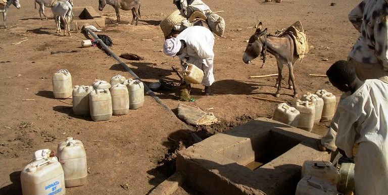 People collect water from a well in Kabkabiya, North Darfur (file photo)