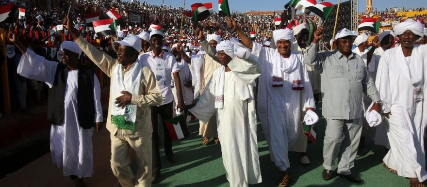 Supporters wave flags during an electoral campaign rally of the ruling National Congress Partyat a stadium in Khartoum, 24 February 2015 (Ashraf ShazlyAFP)