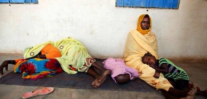 Women wait for medical aid in Darfur (file photo)