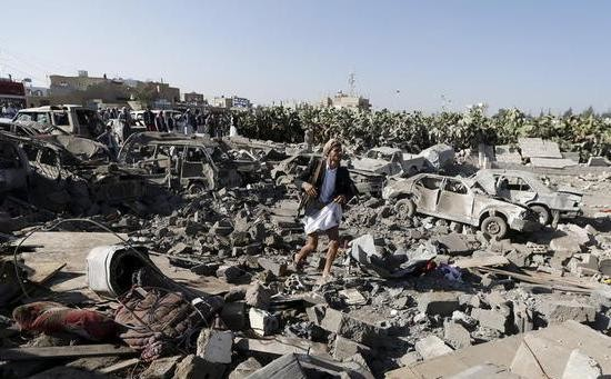 An armed Yemeni walks on rubble of houses destroyed by an air raid near Sanaa Airport (Reuters)