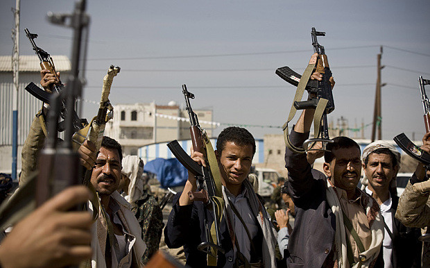 Shiite Houthi rebels raise their weapons during clashes near the presidential palace in Sanaa, 19 January 2015 (Hani Mohammed/AP).