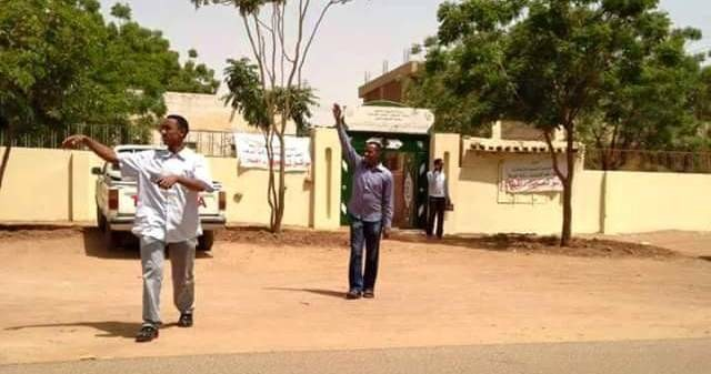 In one of Sudan's cities, men call on passers-by to cast their vote in the poll centre behind during the first election day on 13 April 2015 (file photo)