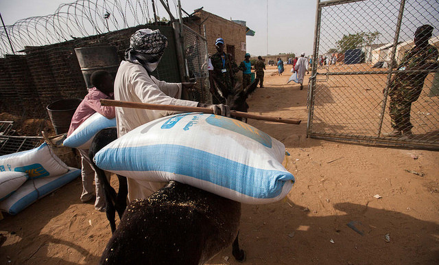 A displaced man carries a bag with millet into the Unamid base in Khor Abeche, South Darfur, where the residents of the nearby camp sought refuge after attacks by a militia on 22 March (Albert González Farran/Unamid).