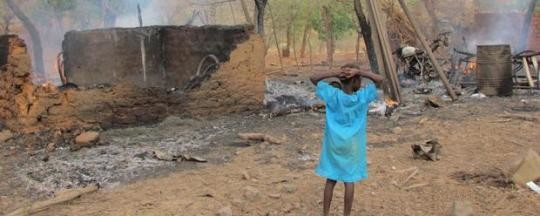 A child looks at what once was a village in Darfur (file photo)