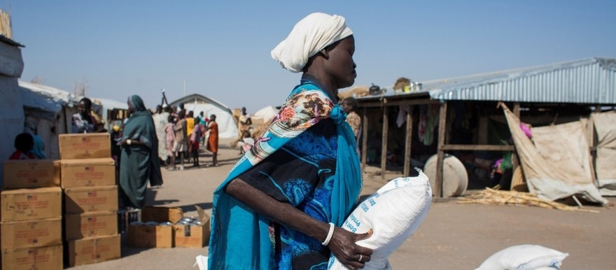 A South Sudanese mother carries a bag of cereals provided by the WFP in in El Agaya refugee camp in White Nile state (Ala Khier/WFP)