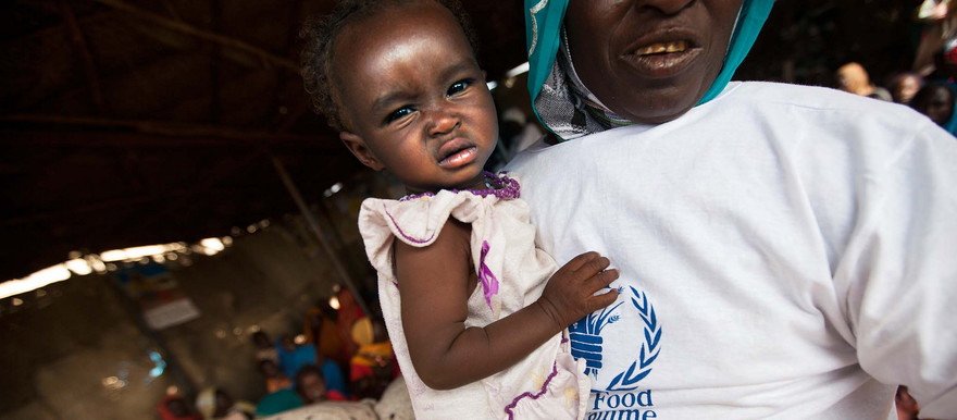 A WFP community volunteer holds a child before being attended in a food distribution center in the Rwanda camp for displaced people in Tawila, North Darfur (Albert Gonzalez Farran/Unamid)