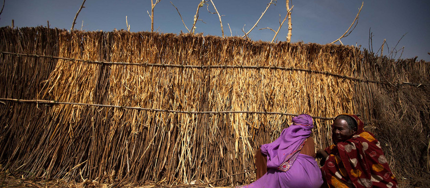 Two women build the fence of a shelter in the Alabassi camp for displaced people, in Mellit, North Darfur (Albert Gonzalez Farran/Unamid)