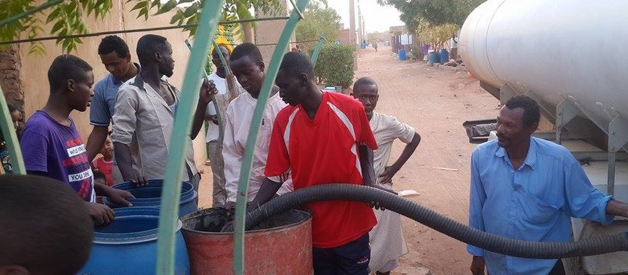 File photo: People fill their buckets with water from a tank during a water shortage in El Azhari district in Khartoum (RD)