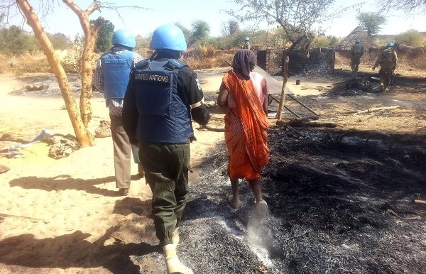 A Unamid peacekeeper interacts with a woman in Mouli village, West Darfur, after attacks in the area (file photo)