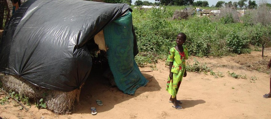 A child stands before a makeshift shelter in a camp for the displaced in Darfur (file photo)