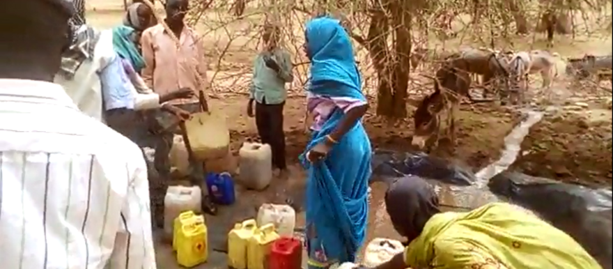 Still of a video recording of a running water engine in Darfur. The local population, and donkeys, have gathered to obtain water (RD, March 2016)