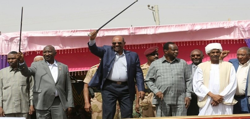 Al Bashir waves his cane during a rally (file photo)