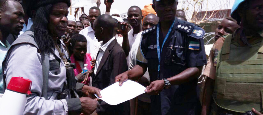 The head of Kalma Camp for the displaced near Nyala, Sheikh Abdelrahman Ali El Tahir, hands a memorandum to a Captain of the Unamid police on behalf of the displaced, during a protest on 2 April. (RD)