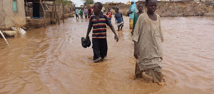 Children wade through flooded streets in Shangil Tobaya, North Darfur, in August 2016 (Ahmed Addouma/Unamid)