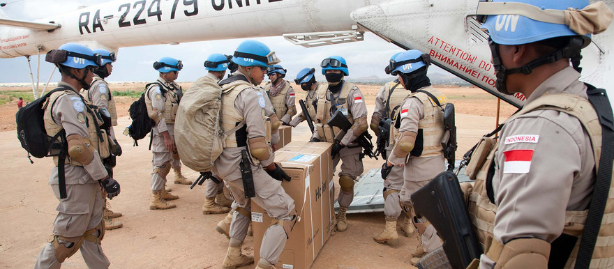 Members of the Indonesian Formed Police Unit, deployed in Kutum by Unamid, unload material from an helicopter in August 2012 (Albert Gonzalez Farran/Unamid)