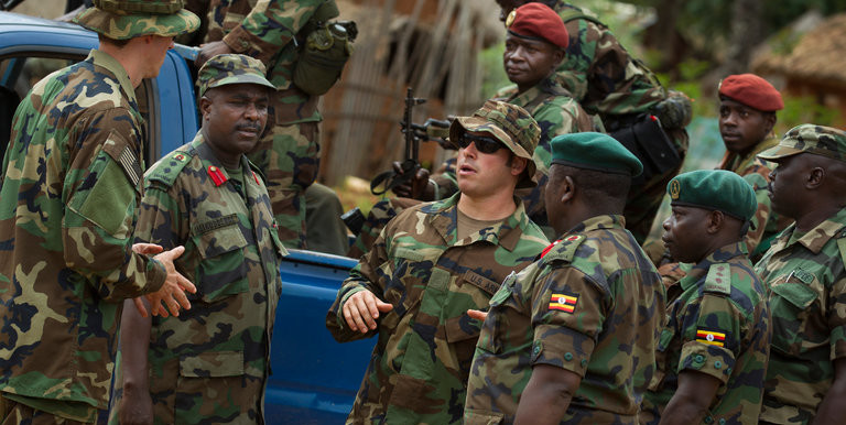 An American Special Forces officer, in sunglasses, speaking with troops from the Central African Republic and Uganda, in Obo, Central African Republic, while searching for Joseph Kony in 2012 (Ben Curtis/Associated Press)