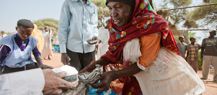 A woman receives sugar from the World Food Program (WFP) in Kassab camp in 2012 (Unamid)