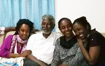 Dr Mudawi at home with his daughters last night (Picture: Submitted by family)