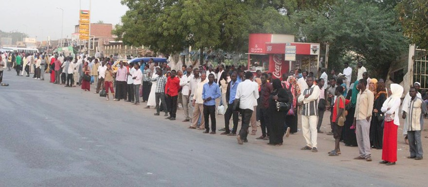 People queue along the road in Khartoum (RD)