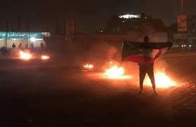 A protester holds a Sudanese flag at a street blockade in Omdurman (RD)