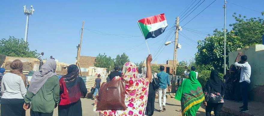 Women in protest march with Sudanese flag (File photo)