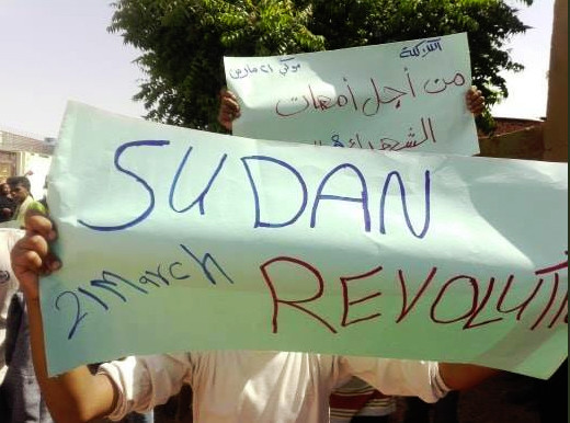 Protesters display placards at a march in Khartoum yesterday