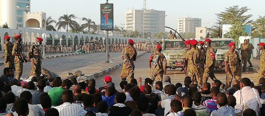 Sudanese soldiers form a protective cordon around demonstrators outside the General Command of the army in Khartoum on Monday
