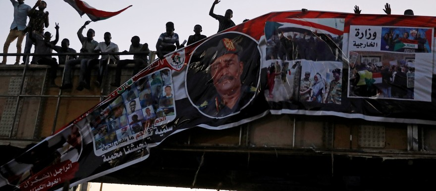 Protesters tear down a banner minutes after it was hung by the Transitional Military Council (TMC) to a railroad bridge near the Defence Ministry in Khartoum on 20 April 2019 (Reuters/Umit Bektas)
