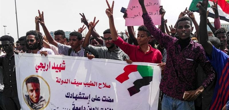 Sudanese protesters with a banner commemorating their friend Salah El Tayeb killed during the uprising (AFP)