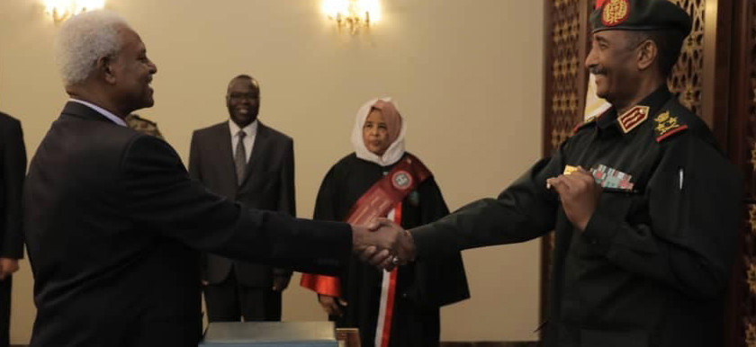 At a ceremony in Khartoum yesterday, Sudan's new Attorney General Tajelsir El Hibir (l) is congratulated by the chairman of Sudan's Sovereign Council, Lt Gen Abdelfattah El Burhan (r), as in the presence of Sudan's first woman Chief Justice, Nemat Kheir (c) (RD correspondent)