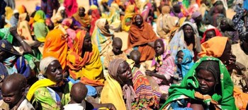Sudanese women sit and await food and non-food items being distributed to them by international humanitarian organisations in the village of Sileia, north of Geneina (file photo)