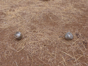 "Two AO-2.5RT submunitions found near the village of Ongolo in South Kordofan. These submunitions have successfully been dispersed from a cluster bomb but failed to detonate (File photo"" Aris Roussinos / HRW)"