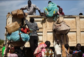Nuba displaced climb onto the back of a truck heading towards Yida refugee camp in South Kordofan (Trevor Snapp/Pulitzer Center)