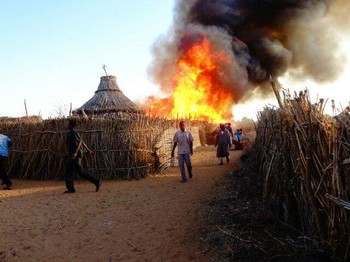 Houses burning in a Darfur camp for the displaced (sudanreeves.org)