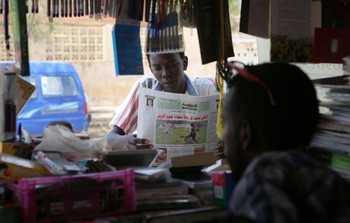 A Sudanese young man looks at newspapers displayed at a kiosk in the capital Khartoum (File photo AFP/Ashraf Shazly.)