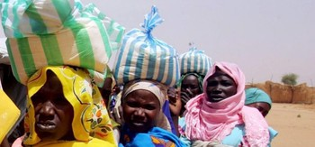 Displaced women in Darfur carrying bags with sorghum flour  (file photo)