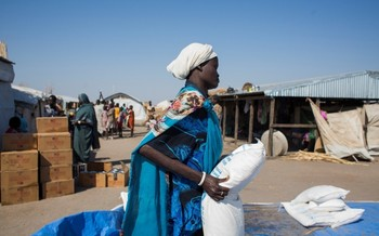 A South Sudanese mother carries a bag of cereal provided by the WFP in in El Agaya refugee camp in White Nile state (Ala Khier / WFP)