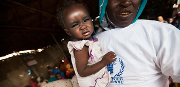 A WFP community volunteer holds a child in a food distribution centre in the Rwanda camp for the displaced in Tawila, North Darfur (Albert  González Farran/Unamid)