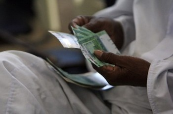A Sudanese man counts bank notes in Khartoum (Mohamed Nureldin Abdallah/Reuters)